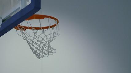 Slow shot of ball passing through basketball net