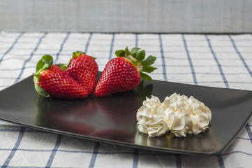 Strawberries and cream on a black plate