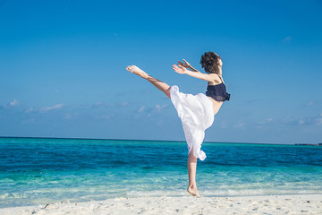 young girl dance at tropical beach