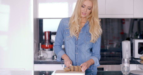 Happy Blond Female Chopping a Bread in the Kitchen