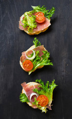 Italian antipasti crostini with ham, salad and tomato