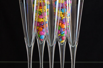 Color chocolate smarties inside the champagne glasses