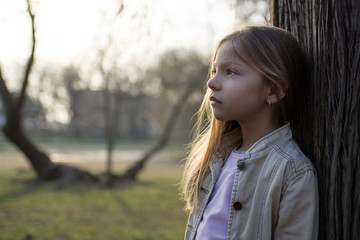 Pensive Little Girl Beside A Tree