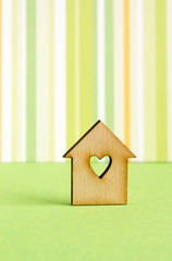 Wooden house with hole in the form of heart on green striped bac