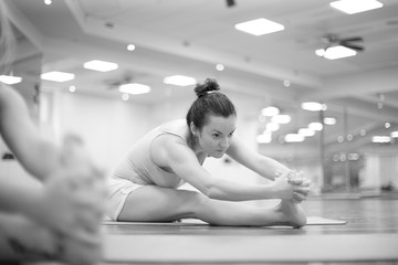 Young woman doing leg stretching exercises in the gym