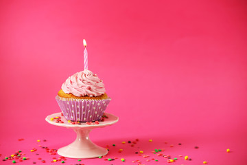 Delicious cupcake on table on pink background