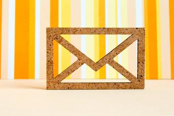 Wooden envelope icon on orange striped background