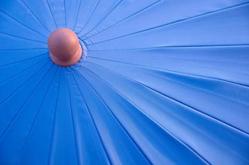 Fragment rozłożonego niebieskiego parasola ogrodowego