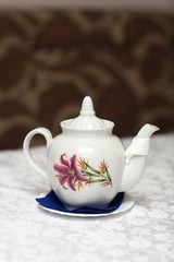 The white teapot with floral ornament
