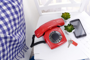 Retro phone on chair in room