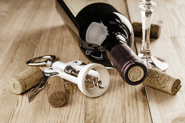 Red wine and corks on wooden background