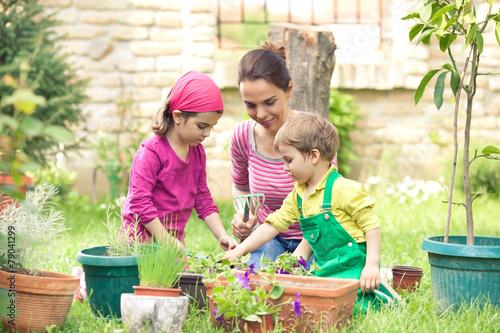 Leinwanddruck Bild Children are helping their mother gardening