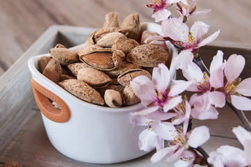 Almonds and flower in a wooden tray for snack