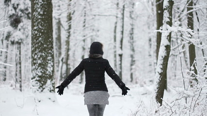Young woman walking in snowy forest, slow motion