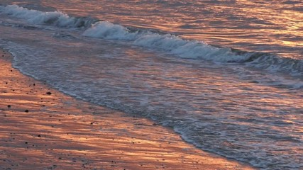 Seascape of waves breaking to shore during sunset