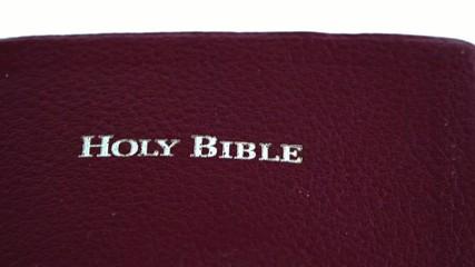 Slowly moving Holy Bible over White Background