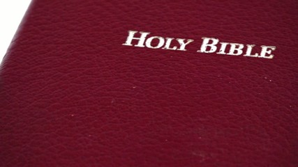 Slowly moving Holy Bible over White Background