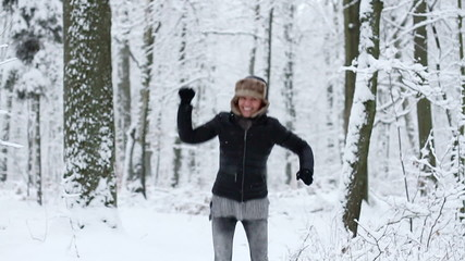 Happy girl jumping in the winter forest, slow motion