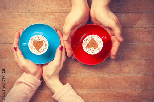 Women and man holding cups of coffee poster