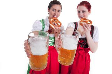 Freundinnen im Dirndl mit Bier und Brezen haben Spaß