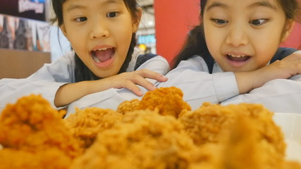 Slow motion of Happy Asian girl with fried chicken in restaurant