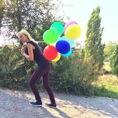 Frau zieht Luftballons auf Berg