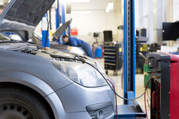 Servicing car air conditioner in auto repair workshop