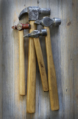 four different hammer on a wooden