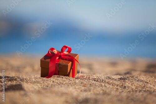 Terracotta color gift box ona beach - 79047075