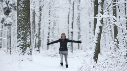 Girl running in a snowy forest, slow motion