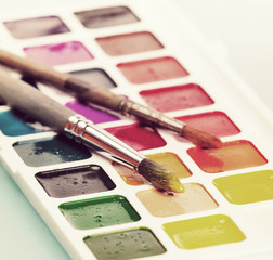 Watercolor paints and brush on the table. Vintage retro hipster