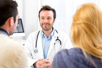 Young attractive doctor advising a young couple of patients
