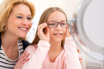 Young little girl trying glasses at the optician w her mother
