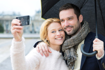 Young couple on holidays under the rain taking selfie