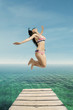 Excited woman in swimsuit jumps at pier