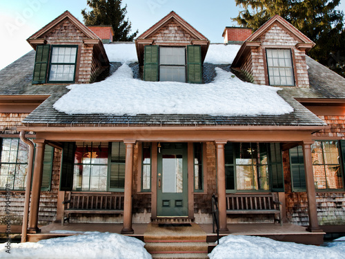 Leinwanddruck Bild front of a winter cottage