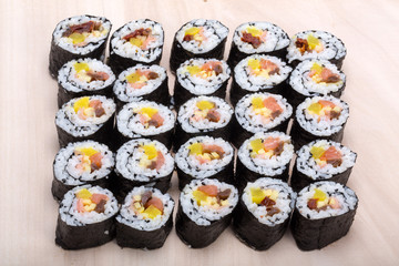 sushi fresh maki rolls isolated on wooden board