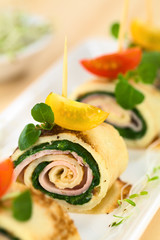 Crepe rolls as finger food filled with spinach and ham