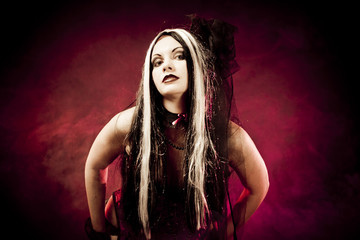 Gothic girl in corset clothes, shot over red smoky background