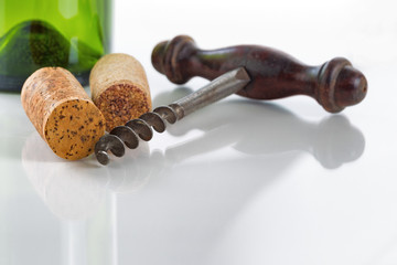 Old corkscrew with corks and wine bottle on glass table