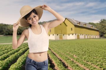 Happy woman standing at farmland