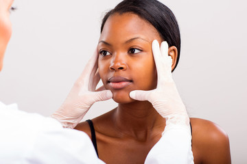 doctor doing skin check on young african woman