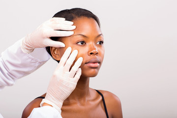 dermatologist checking young african american woman face skin