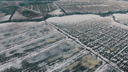 Flying Over Winter Agricultural Fields in Cloudy Weather, aerial