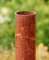 Vertical rusted metal pipe on green