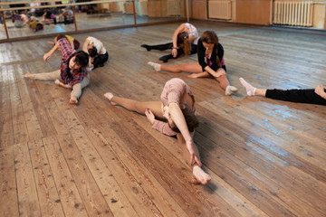 Dancers do workout sitting on the floor at  splits