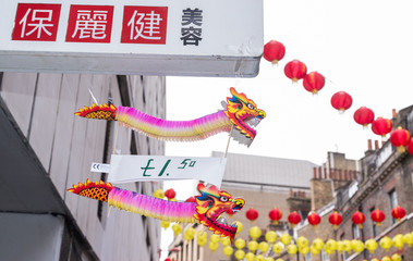 Chinese dragon paper toys hanging from a shop sign