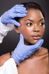 doctor checking african girl face