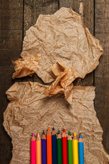 Multicolored pencils and crumpled paper