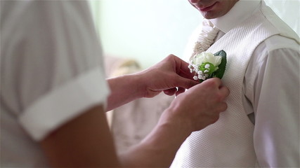 groom corrects the buttonhole